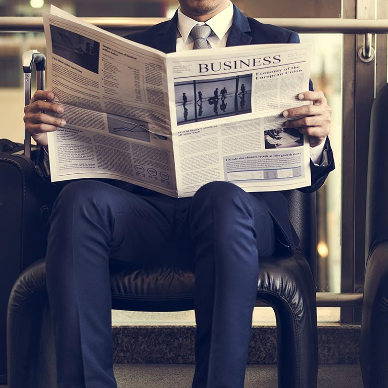 Business man sitting and reading news in a newspaper